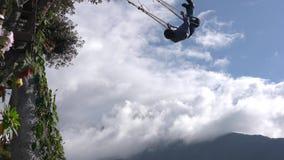 Banos, Ecuador - 20180924 - Frau dreht und wirft Arme weit auf Casa de Arbol Swing über Abgrund gegen Wolken stock video footage