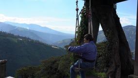 Banos, Ecuador - 20180924 - Frau erhält die Hilfe, die in Casa de Arbol Swing über Abgrund gurtet stock video