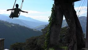 Banos, Ecuador - 20180924 - Mann auf Casa de Arbol Swing über Abgrund mit den Armen weit geworfen stock footage
