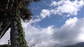 Banos, Ecuador - 20180924 - Mann dreht sich auf Casa de Arbol Swing über Abgrund gegen Wolken stock footage