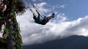 Banos, Ecuador - 20180924 - Mann reitet Casa de Arbol Swing über Abgrund gegen Wolken stock footage