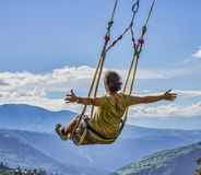 Banos, Ecuador - September 24, 2018 - Person rides swing over an abyss, with a feeling of flying. Banos, Ecuador - September 24, 2018 - Person rides swing over royalty free stock image