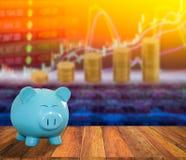Banque bleue de porc sur le fond en bois avec le backgrou de marché boursier de tache floue Photographie stock libre de droits