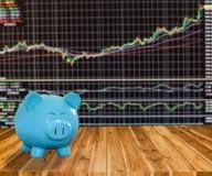 Banque bleue de porc sur le fond en bois avec le backgrou de marché boursier de tache floue Photos libres de droits