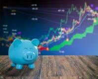 Banque bleue de porc sur le fond en bois avec le backgrou de marché boursier de tache floue Images stock