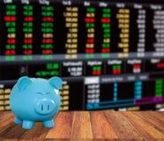 Banque bleue de porc sur le fond en bois avec le backgrou de marché boursier de tache floue Photo libre de droits