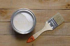 Banque de la peinture et de la brosse blanches sur une table en bois photographie stock libre de droits
