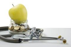 Banque en verre avec les pièces de monnaie, la pomme verte et le stéthoscope médical Medi Images stock
