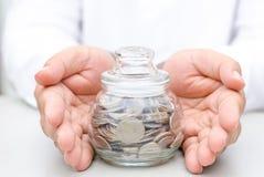 Banque en verre de pot d'argent protégée par main masculine Image stock