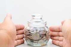 Banque en verre de pot d'argent protégée par main masculine Photo libre de droits