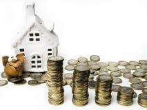 Banque, pièces de monnaie et maison de porc sur la table blanche économisez et investissement pour le concept de maison d'achat à images libres de droits