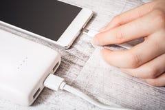 Banque se reliante de puissance de main femelle avec le téléphone de PMobile pour recharger la basse batterie, vue courbe Photographie stock