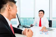 Banqueiro asiático que aconselha o investimento financeiro Fotos de Stock Royalty Free