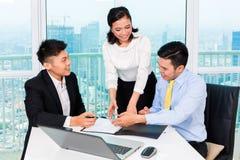 Banqueiro asiático que aconselha o homem no escritório Foto de Stock Royalty Free