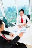 Banqueiro asiático que aconselha o investimento financeiro Fotografia de Stock Royalty Free