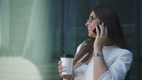 Banqueiro principal seguro novo da mulher de negócios que fala no telefone, guardando o copo de café que está na rua filme