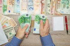 Banquero que cuenta euros en su tabla de la oficina, imagen de archivo