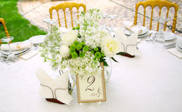 Banquet. A view of a round banquet table with napkins and silverware set and a colorful flower centerpiece Stock Photo