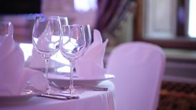 Banquet decorated table, with cutlery. Wedding decor in the banquet hall. Serving of a festive table, plate, napkin. Knife, fork. Table setting decoration stock video footage
