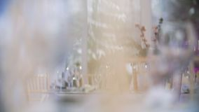 Banquet decorated table in restaurant. Winter style decor in banquet hall. Focusing on glasses and plates stock video footage