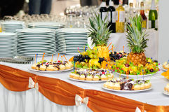 Banquet dessert table. Served banquet table with small fancy cakes and fruits Stock Photos