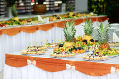 Banquet dessert table. Served banquet table with small fancy cakes and fruits Royalty Free Stock Image