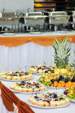 Banquet dessert table. Served banquet table with small fancy cakes and fruits Royalty Free Stock Photos