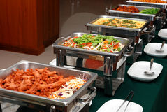 BANQUET MEALS. And Metallic banquet meal trays served on tables stock photography