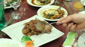 Banquet o convidado que toma a carne fritada gorda apetitosa do prato na tabela do restaurante filme