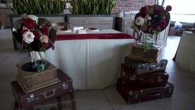Banquet o salão com as decorações para o gramofone do casamento A com as flores em decorações do casamento das malas de viagem vídeos de arquivo