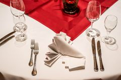 Banquet with red table setting tablecloth white dishes silver cutlery glasses and decorations white copy text space card. Banquet with red table setting Red Royalty Free Stock Photo