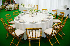 Banquet table. A view of a round banquet table with napkins and silverware set and a colorful flower centerpiece Stock Photo