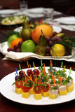 Banquet table. Canape (cheese, tamato, bacon, grapes) and fruit basket with apple, orange, grapes on a background (focus on canape Stock Image