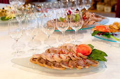 Banquet Table Appetizers. Banquet table set with wine glasses and platters of sliced meat roll ups stock photos