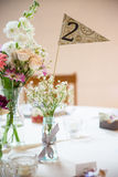 Banquet table centerpiece. Floral centerpieces on a banquet table with a number two flag Royalty Free Stock Image