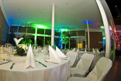 Banquet Table With Colors. Set banquet table with chairs all in white. Multicolored lights at the other side of the room in the background stock photo