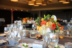Banquet Table and Flowers. Banquet or Wedding Reception Table with wine glasses and orange floral centerpiece stock images