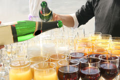 Banquet table with Fougeres. At the banquet table with Fougeres and wine glasses with the juice of red wine and champagne bottles with the hands above the table Stock Photos