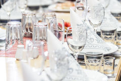 A banquet table with glasses, dishes and serviettes. A part of banquet table with glasses, dishes, serviettes, silverware and salt-cellar Stock Images