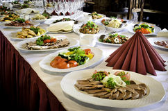 Banquet Table with Much Food. A long table with many platters of food for a party or celebration royalty free stock photography