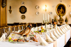 Banquet Table with Pheasant. A long banquet table with fold napkins and stuffed pheasant decoration royalty free stock photography
