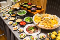 Banquet table with salads and cheese assortment and vegetables. Cut into plates stock photo