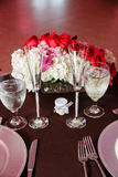 Banquet table settings and flowers. Details of a banquet table setting including plates, glasses, silverware and decorative flowers and roses Stock Photo