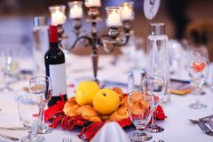 Banquet table with yellow quinces, buns or cakes and bottle of wine gathered in traditional Romanian towel. Holiday table decorated with traditional Moldovan royalty free stock image