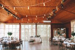 Banquet wooden hall for a rustic wedding with round decorated tables, Viennese chairs with flowered leaves and stock photos