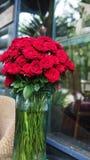 Banquete de las rosas rojas en florero fotografía de archivo libre de regalías