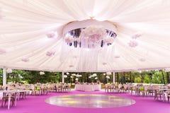 Banquetee el pasillo para una boda con una bóveda blanca Imagen de archivo libre de regalías