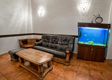 Banquettes simple interior with leather sofa and wooden table. A large aquarium Stock Photography