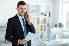 Banquier avec le téléphone et le papier photos stock