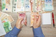 Banquier comptant la Lire turque à sa table de bureau, Photo stock